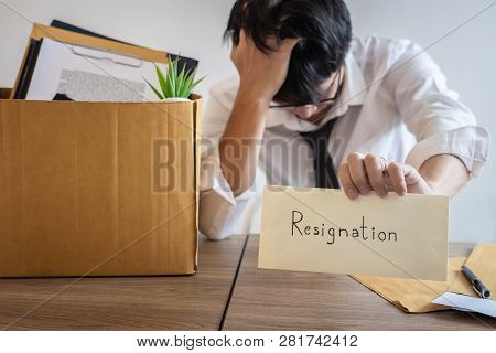 Stressed businessman will being resignation and packing belongings company and files into brown cardboard box, changing and resigning from work concept. poster