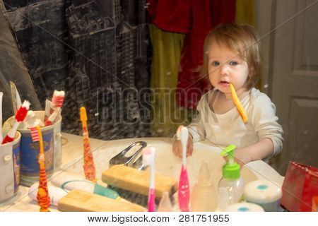 View Through A Dirty Toothpaste-spattered Mirror On A Little Baby Girl. The Child Brushes His Teeth,