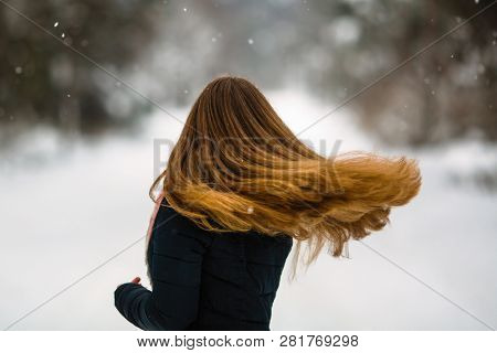 Girl's long hair. Fluttering beautiful ?urls of young woman in winter outdoors.
