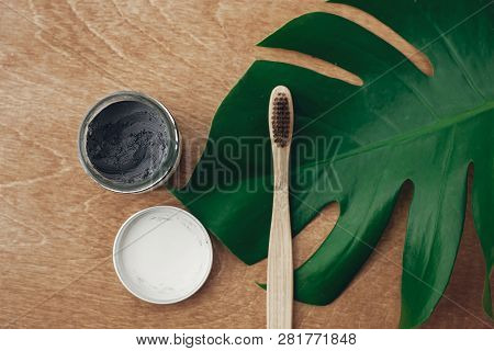 Natural Toothpaste Activated Charcoal And Bamboo Toothbrush On Wooden Background With Green Monstera