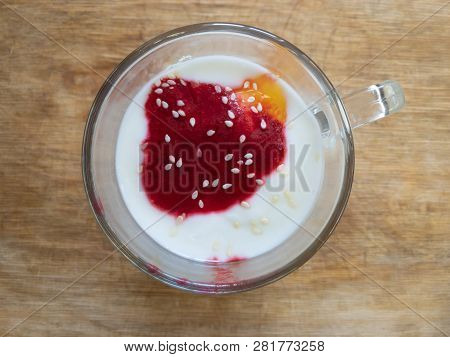 Top View On A Glass Of Yogurt Topped With Honey, Raspberries Mash And Sesame Seed