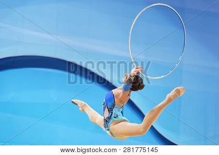 KIEV, UKRAINE - AUGUST 28, 2013:  Unidentified female gymnast performs with hoop during 32nd Rhythmic Gymnastics World Championships. The event is held in Palace of Sport