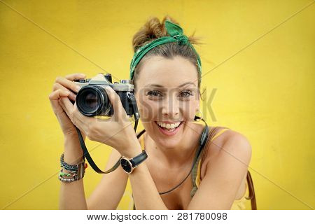 Young stylish woman taking photos outdoors with vintage camera on colored background