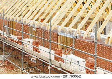 Construction Site In Uk With A House Built From Brick And Timber, Featuring Brickwork, Roof Trusses
