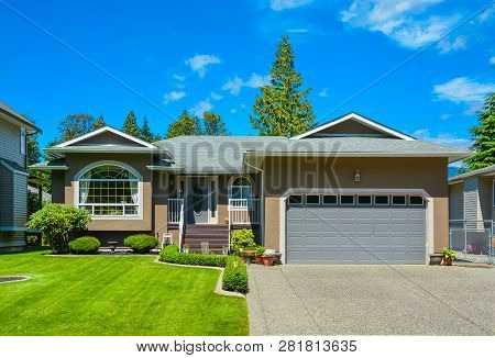 Suburban Family House With Nice Lawn In Front, Wide Garage Door, And Concrete Driveway