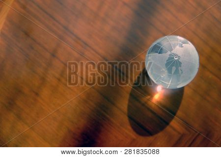 Top View Of Crystal World Map Glass Globe Ball On Glossy Wooden Table