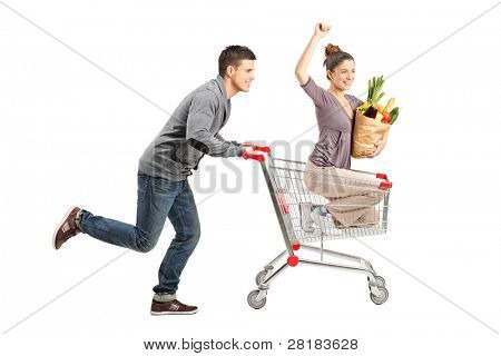 Person pushing a happy woman in a shopping cart with paper bag ful with food isolated on white background