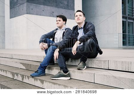 Two Male Teenage Friends Or Brothers Two Male Teenage Friends Sitting On Concrete Steps Or Staircase