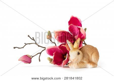 An image of an easter bunny sitting by some red magnolia flowers