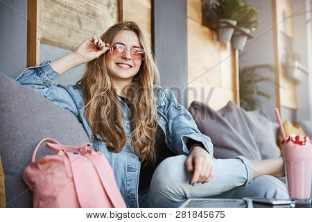 Attractive And Joyful Fair-haired Female Coworker In Denim Jacket, Sitting In Carefree Pose On Sofa