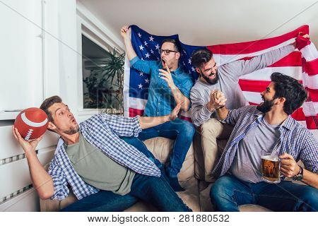 Male Friends Watching Tv And Cheering Sport Games On Sofa At Home. Group Of Friends Watching America