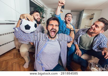 Men Watching Sport On Tv Together At Home Screaming Cheerful. Group Of Friends Sitting On The Couch