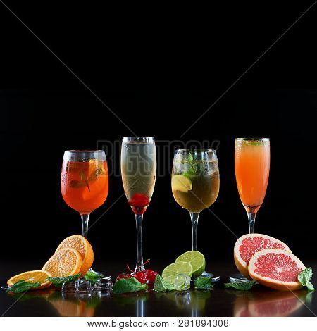 Composition With Four Different Shapes Crystal Cocktail Glasses With Cold Drinks, Orange, Lime And G