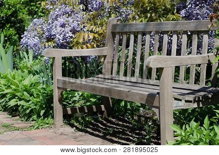 An Unoccupied Bench Sites In A Garden In The Spring