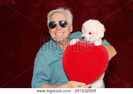 Valentines Day. A man holds a Velvet Valentines Box of Chocolates and a Small White dog in a Photo Booth. Valentines day gift of candy and puppy.
