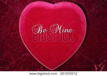 Valentines Day. Red Velvet Heart Shaped Valentines Day Chocolates Box. On Burgundy Red Velvet background.  Text reads, Be Mine