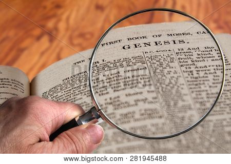 Hand Holding Magnifying Glass Over An Old Bible Opened To The Famous Chapter Of Genesis. This Transl