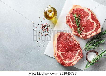 Fresh Meat On Kitchen Table Top View. Raw Beef Steak And Spices For Cooking.