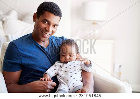 Close up of young adult black father sitting in an armchair holding his three month old baby son, smiling to camera, front view poster