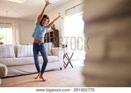 Pre-teen girl dancing and singing along to music on TV in the living room at home, three quarter length