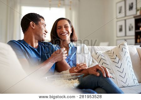 Young adult mixed race couple sitting on the sofa in their living room laughing and eating popcorn, selective focus