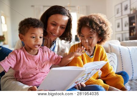 Excited toddler boy sitting on his mother's knee reading a book in the living room with his older sister, close up