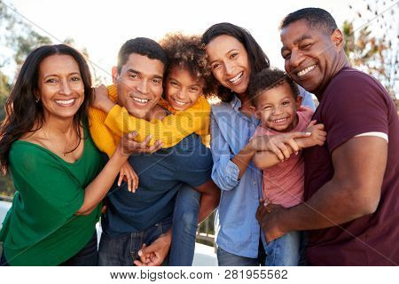 Mixed race three generation family playing together in the garden, smiling to camera