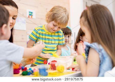 Children Dough Play In Daycare Centre. Kids With Teacher Mold From Plasticine In Kindergarten. Littl