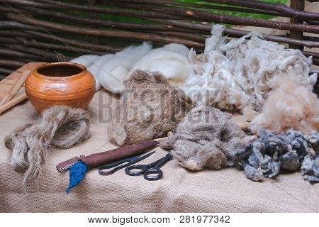Traditional earthenware crockery pot, packs of sheep wool, hand shears, scissors and other tools on linen covered table. Medieval reconstruction poster