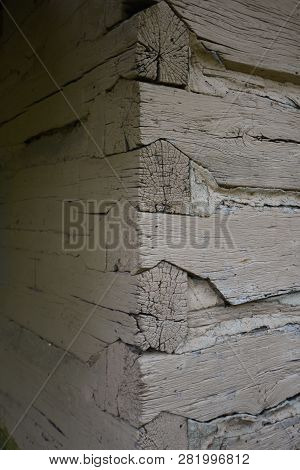 Corner of a log cabin with interlocking logs, An old cabin exposes the notched corners of the weathered wood logs poster