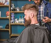 Hairstyle service concept. Hipster bearded client got hairstyle. Barber with trimmer or clipper shaved neck of client. Barber with clipper works on hairstyle for bearded man, barbershop background poster