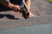 Roofing Construction. Roofer installing asphalt shingles on house construction roof corner with hammer and nails. poster