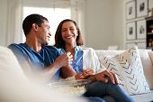 Young adult mixed race couple sitting on the sofa in their living room laughing and eating popcorn, selective focus poster