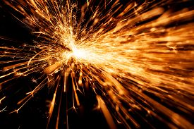 Bright Orange And Yellow Sparks On A Black Background. A Stream Of Bright Sparks From Metal Cutting