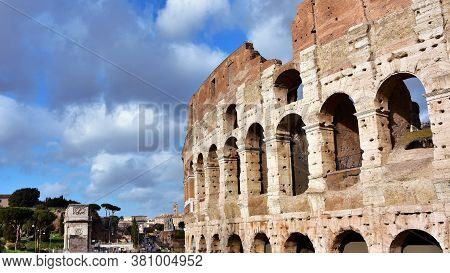 Coliseum And Roman Archeological Area With Cloudy Sky