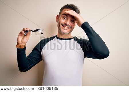 Young handsome optical man showing glasses standing over isolated white background stressed with hand on head, shocked with shame and surprise face, angry and frustrated. Fear and upset for mistake.
