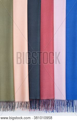 Several Luxurious Women's Cashmere Shawls, Scarves In Multi-colored Tones On A Metal Hanger. Studio