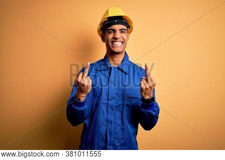 Young handsome african american worker man wearing blue uniform and security helmet Showing middle finger doing bad expression, provocation and rude attitude. Screaming excited