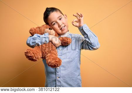 Young little boy kid hugging teddy bear stuffed animal over yellow background doing ok sign with fingers, excellent symbol