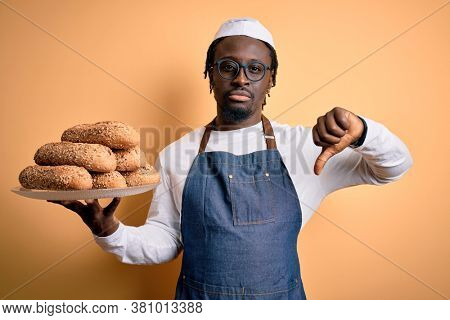 Young african american bakery man holding tray with healthy wholemeal bread with angry face, negative sign showing dislike with thumbs down, rejection concept