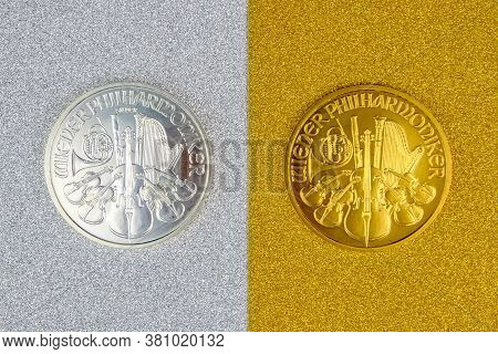 Silver And Golden Austrian Mint Phillharmoniker One Ounce Coins Laying On Silver And Golden Backgrou
