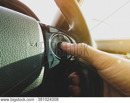 Driver Pressing Cruise Control Button Switch On Steering Wheel Of A Car