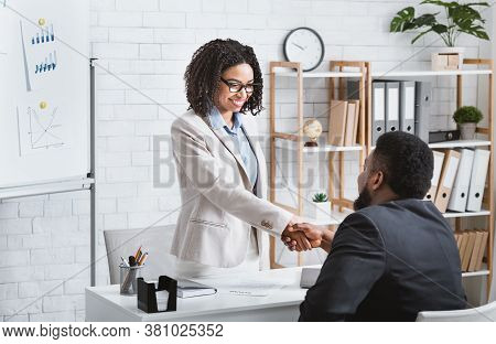 Black Hiring Manager Shaking Hands With Successful Vacancy Candidate After Work Interview At Modern