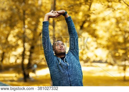 Millennial Black Sportsman Stretching His Arms Before Jogging At Park On Beautiful Autumn Morning