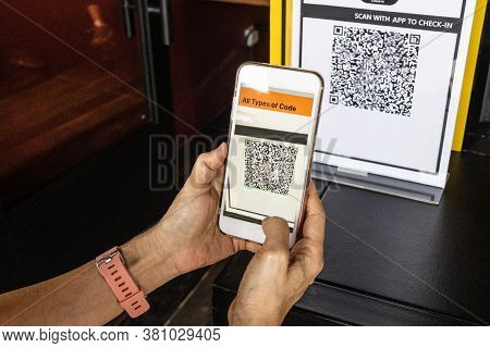 Modified Inactive Qr Code Used.  Person Scanning Qr Code With Smartphone To Register Details Before