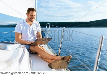 Happy Man On Yacht Sitting With Laptop Working Living On Sailboat During Summer. Liveaboard Tour. Em