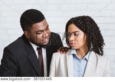 Sexual Harassment In Office Concept. Male Boss Touching His Disgusted Female Subordinate At Workplac
