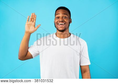 Hello. Cheerful African Man Waving Hand Greeting Smiling To Camera Standing Over Blue Studio Backgro