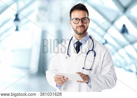 Shot Of Male Doctor Standing On The Clinic's Foyer And Using Digital Tablet While Working.