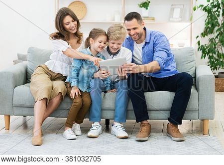 Happy Family Of Four Using Tablet Computer Together Sitting On Couch At Home. Weekend Leisure Concep